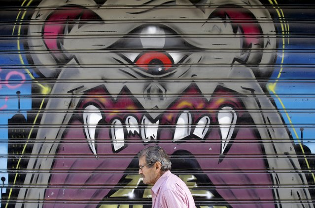 A man walks past graffiti painted on a closed shop at Monastiraki area in central Athens, Greece, July 7, 2015. Greece faces a last chance to stay in the euro zone on Tuesday when Prime Minister Alexis Tsipras puts proposals to an emergency euro zone summit after Greek voters resoundingly rejected the austerity terms of a defunct bailout. (Photo by Christian Hartmann/Reuters)