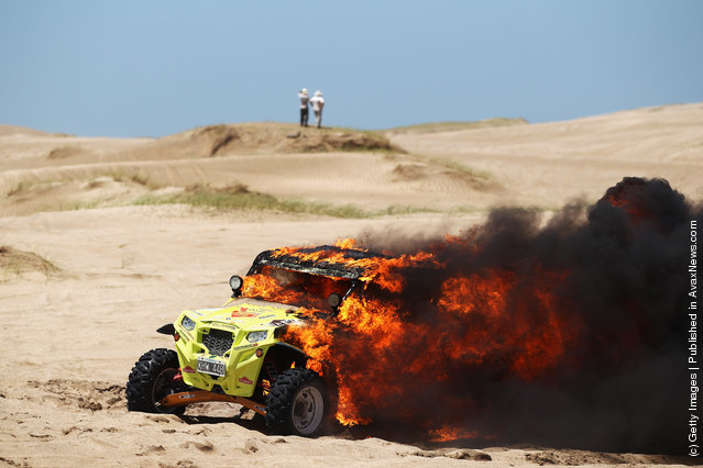 The burning Polaris of Jose Antonio Blangino of Argentina sits in the sand dunes during stage one of the 2012 Dakar Rally