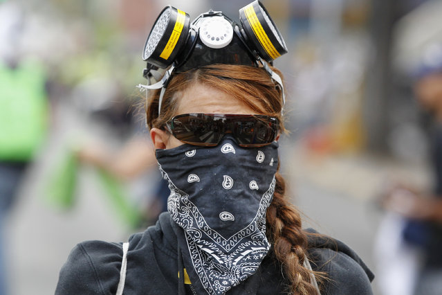 An anti-government protester takes part in a march against education reforms in Caracas April 26, 2014. Venezuelan justice determined on Friday that Venezuelans who want peaceful protest must request permission from local governments to prevent the scattered forces, amid a wave of violent protests against President Nicolas Maduro. (Photo by Christian Veron/Reuters)