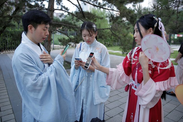 """Young people dressed in """"Hanfu"""", or Han clothing, use their mobile devices at an event marking the traditional Qixi festival, the Chinese equivalent of Valentine's Day, at a park in Beijing, China, August 7, 2019. (Photo by Jason Lee/Reuters)"""