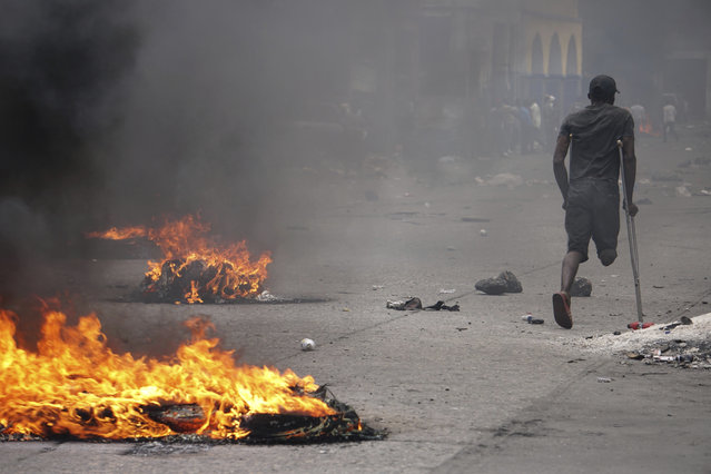 A protester on crutches passes burning tires during a demonstration to demand the resignation of President Jovenel Moise in Port-au-Prince, Haiti, Monday, June 10, 2019. Opposition leaders in Haiti launched a two-day strike that paralyzed the country's capital amid another day of protests demanding that President Jovenel Moise resign over corruption allegations. (Photo by Edris Fortune/AP Photo)