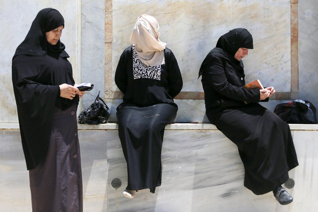 Palestinian women read the Koran as another covers her face for protection from the sun on the fourth Friday of the holy month of Ramadan at the compound known to Muslims as the Noble Sanctuary and to Jews as Temple Mount, in Jerusalem's Old City July 10, 2015. (Photo by Ammar Awad/Reuters)