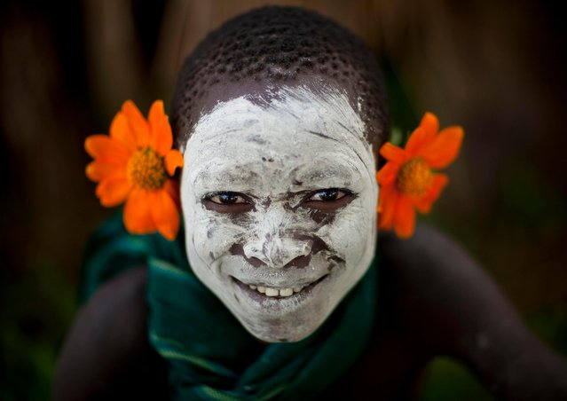 Children are often known to decorate themselves with plants and blossoms from the surrounding village. (Photo by Eric Lafforgue/Exclusivepix Media)