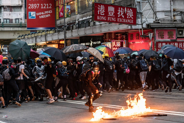 A pro-democracy protester throws a Molotov cocktail during a clash With police at a demonstration in Wan Chai district on October 6, 2019 in Hong Kong, China. Hong Kong's government invoked emergency powers on Friday to introduce an anti-mask law which bans people from wearing masks at public assemblies as the city remains on edge with the anti-government movement entering its fourth month. Pro-democracy protesters marked the 70th anniversary of the founding of the People's Republic of China in Hong Kong as one student protester was shot in the chest in the Tsuen Wan district during with mass demonstrations across Hong Kong. Protesters in Hong Kong continue to call for Chief Executive Carrie Lam to meet their remaining demands since the controversial extradition bill was withdrawn, which includes an independent inquiry into police brutality, the retraction of the word riot to describe the rallies, and genuine universal suffrage, as the territory faces a leadership crisis. (Photo by Anthony Kwan/Getty Images)