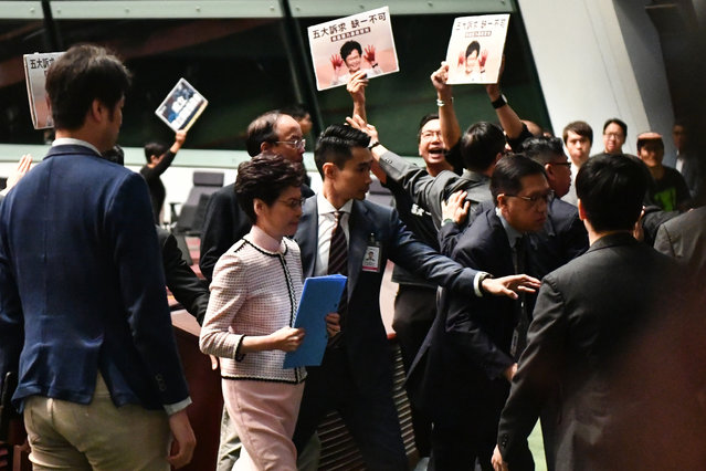 Hong Kong's Chief Executive Carrie Lam (2nd L) leaves the chamber for a second time while trying to give her annual policy address as she is heckled by pro-democracy lawmakers (at background) at the Legislative Council (Legco) in Hong Kong on October 16, 2019. Hong Kong leader Carrie Lam was to unveil a closely watched State of the Union-style speech on October 16 aimed at winning hearts and minds after four months of seething pro-democracy protests. (Photo by Anthony Wallace/AFP Photo)