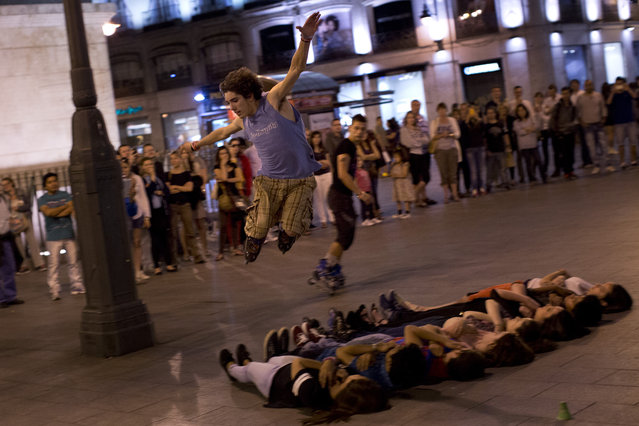 A roller skater jumps over eight people lying on the ground, at Sol square in the center of Madrid, Spain, Tuesday, May 6, 2014. (Photo by Emilio Morenatti/AP Photo)