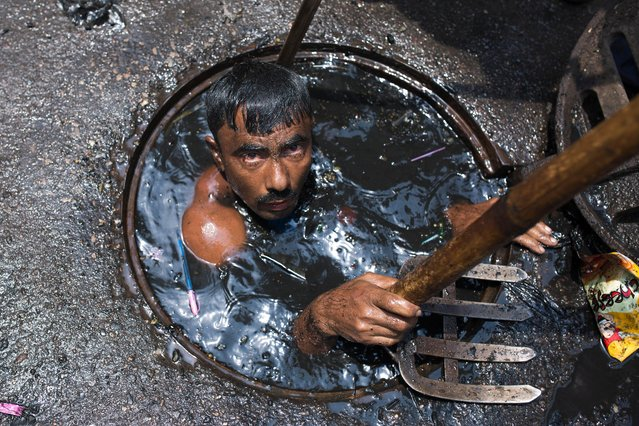 A sewer cleaner of Dhaka City Corporation cleaning out the city's sewers on May 03, 2017 in Dhaka, Bangladesh. Despite a rise in the number of deaths of manhole workers every year, workers regularly go into the manholes without any protective gear. (Photo by Zakir Chowdhury/Barcroft Images)