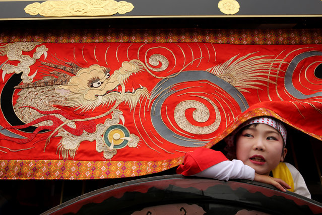 Japanese flower cart girl looks under the dragon banner during the Mikuini annual festival on May 20, 2014 in Sakai, Japan. The annual festival takes place from May 19-21 and is attended by thousands of visitors. During the festival people dressed in traditional Japanese costumes pull carts carrying 6 meter high dolls of Japanese historical figures through the narrow streets. The origins of the festival are unclear but its history can be traced back more than 250 years. (Photo by Buddhika Weerasinghe/Getty Images)