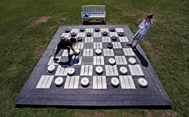 In this Thursday, July 2, 2015 photo, Madi Clark, 8, of Ottawa, makes a move against her brother, Connor, while playing checkers on a giant game board at the Mount Washington Resort in Bretton Woods, N.H. (Photo by Charles Krupa/AP Photo)