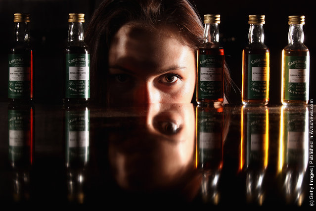 Victoria Kasperovich, an employee at McTear's Auctioneers, views a very rare collection of five Cadenhead Irish whiskey miniatures