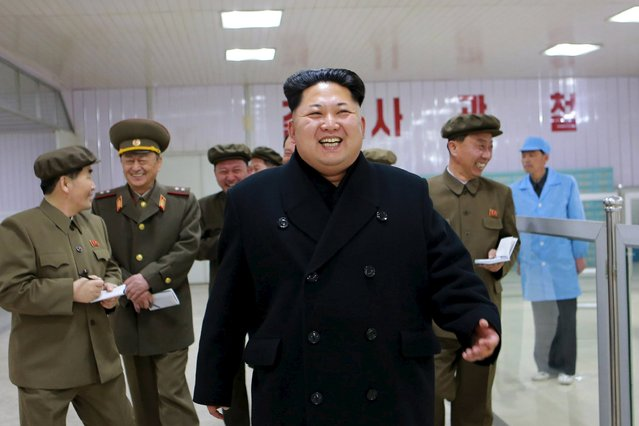 North Korean leader Kim Jong Un (front) laughs during a visit to the Pyongyang Weak-current Machine Plant, in this undated photo released by North Korea's Korean Central News Agency (KCNA) in Pyongyang on April 8, 2015. (Photo by Reuters/KCNA)