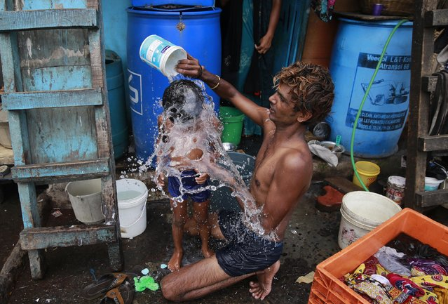 A man bath his son on a hot afternoon in a slum in Mumbai, India, Monday, May 23, 2016. Authorities in a parched western Indian state sprinkled water in the streets and awaited the arrival of a special water train on Saturday, two days after temperatures reached a record-high 51 degrees Celsius (124 Fahrenheit). (Photo by Rafiq Maqbool/AP Photo)