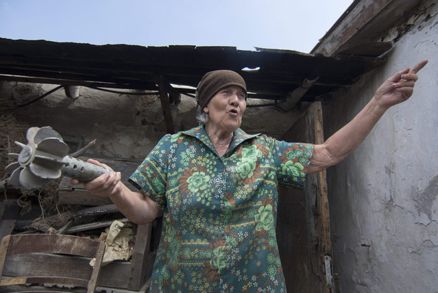 Tamara Kutnenko, 71, shows a part of a spent mortar shell next to her damaged house after recent shelling, on a territory controlled by Ukrainian army, some 15 km to the front line, in the urban village of Novotroitskoe, Donetsk area, Ukraine, 22 July 2015. Pro-Russian separatists have said they will withdraw all of their heavy weapons from the conflict zones of eastern Ukraine on 26 July in accordance with an agreement with the Organization for Security and Cooperation in Europe (OSCE). (Photo by Sergey Vaganov/EPA)