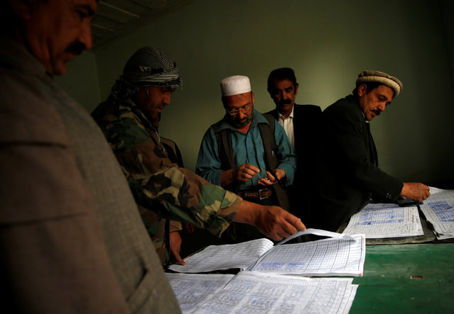 Workers sign attendance sheets as they arrive for work at the Jabal Saraj cement factory in Jabal Saraj, north of Kabul, Afghanistan April 19, 2016. (Photo by Ahmad Masood/Reuters)