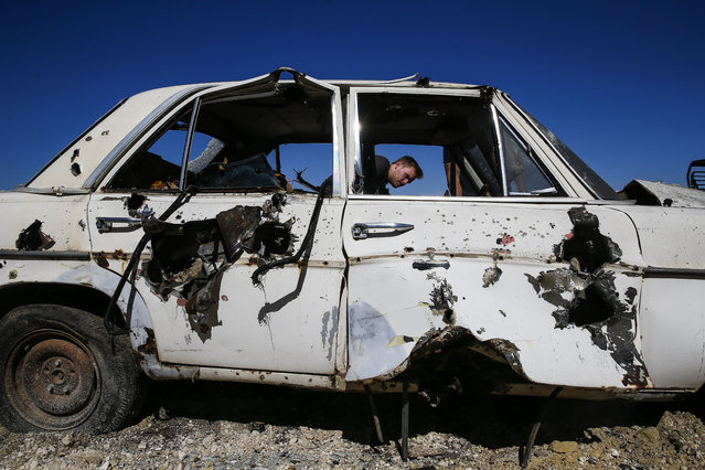 In this May 24, 2017, photo, Spencer Jones looks at the damage he and other members of his group did to a car with several rounds of artillery and machine guns during an Allies and Axis all-day experience in Uvalde, Texas. (Photo by Michael Ciaglo/Houston Chronicle via AP Photo)