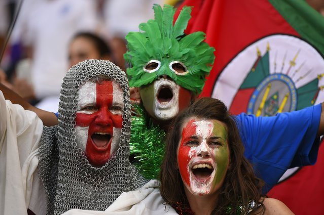 An England fan (L) with his face painted in the colours of his national flag and wearing a chain mail costume cheers next to an Italian fan prior to a Group D football match between England and Italy at the Amazonia Arena in Manaus during the 2014 FIFA World Cup on June 14, 2014. (Photo by Fabrice Coffrini/AFP Photo)
