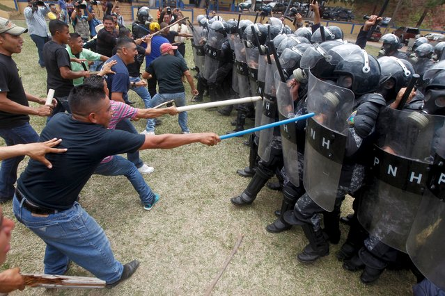 Mock rioters clash with members of the police unit for riot for law and order restoration, during a drill at a base in Tegucigalpa, Honduras, July 30, 2015. About 400 policemen were trained by military to respond to emergencies and to contain violent protests, local media reported. (Photo by Jorge Cabrera/Reuters)