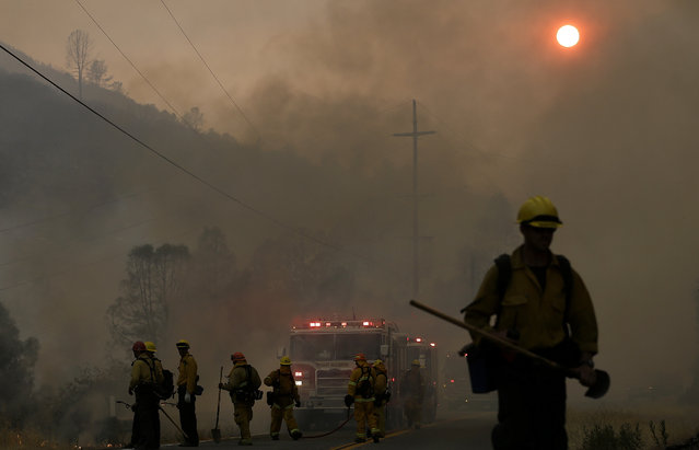 Firefighters walk under smoke from fires along Morgan Valley Road near Lower Lake, Calif., Friday, July 31, 2015. (Photo by Jeff Chiu/AP Photo)