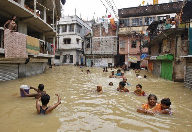 Flood-affected people wade through a flooded street at West Midnapore district in West Bengal, India, August 4, 2015. (Photo by Rupak De Chowdhuri/Reuters)