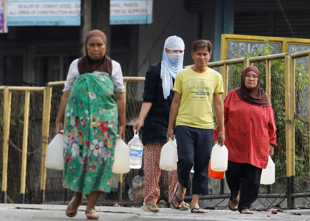Residents who were displaced due to fighting between government soldiers and the Maute militant group, carry plastic containers of water in Marawi City in southern Philippines May 28, 2017. (Photo by Erik De Castro/Reuters)