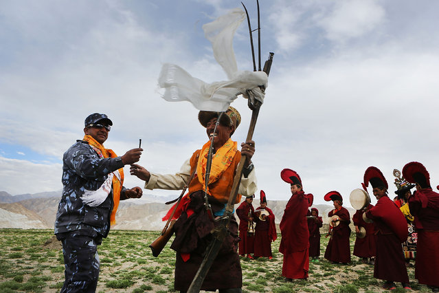 Traditionally dressed representatives of Upper Mustang's villages fire antique guns to chase demons from the city during the Tenchi Festival on May 27, 2014 in Lo Manthang, Nepal. The Tenchi Festival takes place annually in Lo Manthang, the capital of Upper Mustang and the former Tibetan Kingdom of Lo. Each spring, monks perform ceremonies, rites, and dances during the Tenchi Festival to dispel evils and demons from the former kingdom. (Photo by Taylor Weidman/Getty Images)