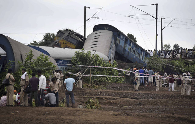 People gather at the site of a train accident near the town of Harda in Madhya Pradesh state, India, Wednesday, August 5, 2015. (Photo by AP Photo)