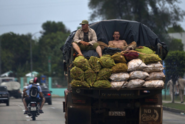 Workers ride on the back of a truck loaded with vegetables to sell at the market in Havana, Cuba, Tuesday, April 21, 2015. (Photo by Ramon Espinosa/AP Photo)