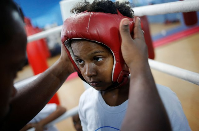 Teacher Alan (L) puts helmet on a child during an exercise session at a boxing school, in the Mare favela of Rio de Janeiro, Brazil. (Photo by Nacho Doce/Reuters)