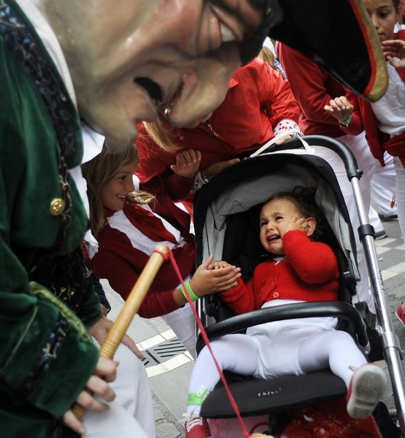 A baby cries as a cabezudo (big-head) looks at her during the San Fermin Festival in Pamplona, northern Spain, on July 10, 2014. The festival is a symbol of Spanish culture that attracts thousands of tourists to watch the bull runs despite heavy condemnation from animal rights groups. (Photo by Rafa Rivas/AFP Photo)