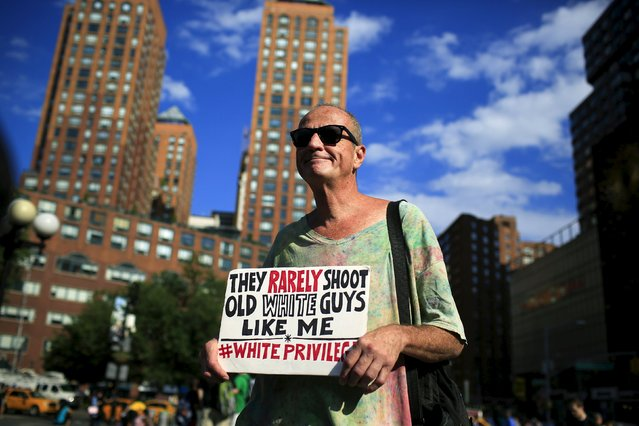 A man with a poster takes part in a small rally at Union Square marking the first anniversary of the death of Michael Brown, an unarmed black teenager shot dead by a white police officer in Ferguson, Missouri a year ago, in New York August 9, 2015. (Photo by Eduardo Munoz/Reuters)