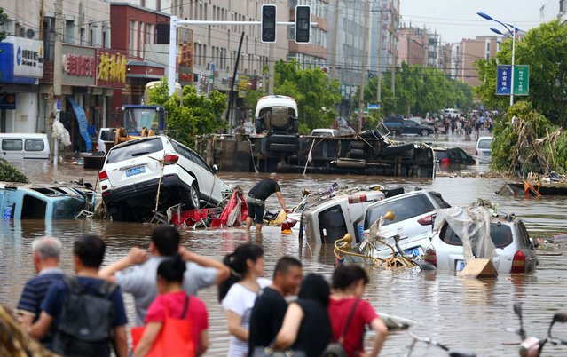 This photo taken on July 15, 2017 shows people cleaning up after flooding in Yongji, a county under the administration of the city of Jilin in northeast China' s Jilin province. (Photo by AFP Photo/Stringer)
