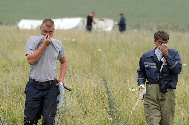 People search for bodies on July 18, 2014 at the site of the crash of a Malaysian airliner carrying 298 people from Amsterdam to Kuala Lumpur, near the town of Shaktarsk, in rebel-held east Ukraine. Pro-Russian separatists in the region and officials in Kiev blamed each other for the crash, after the plane was apparently hit by a surface-to-air missile. (Photo by Dominique Faget/AFP Photo)