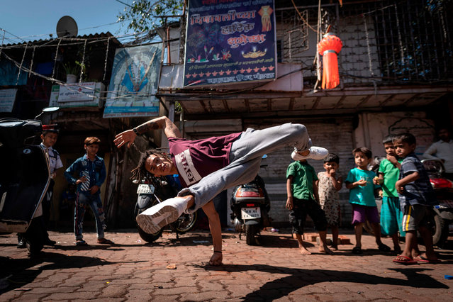 Brasilian dancer Mateus Melo performs in the streets during a photo session in Mumbai on November 7, 2019, ahead of the Red Bull BC One world championship. Mumbai will host the world's most prestigious one-on-one battle. Mumbai will see 16 of the world's best breakers go head to head to take the belt and earn the title of Red Bull BC One World Champion. (Photo by Lionel Bonaventure/AFP Photo)