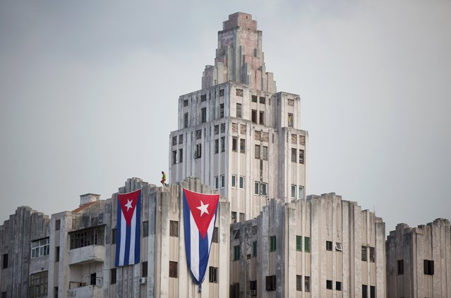 A man hangs Cuban flags on a building near the U.S embassy, (not pictured) in Havana, Cuba August 11, 2015. (Photo by Alexandre Meneghini/Reuters)