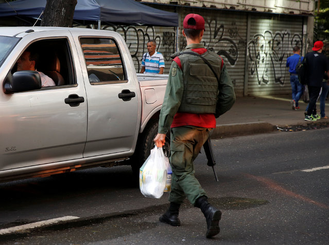 A Venezuelan soldier walks while holding a bag of food on a street in Caracas, Venezuela, June 23, 2016. (Photo by Mariana Bazo/Reuters)