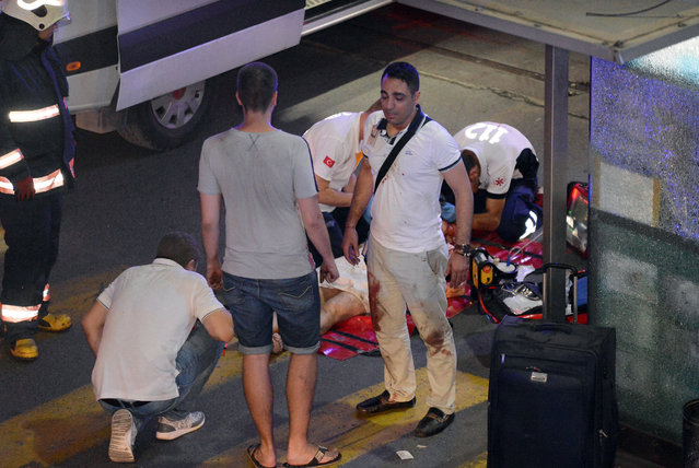 Turkish rescue services help a wounded person outside Ataturk Airport in Istanbul, Tuesday, June 28, 2016. Two explosions have rocked Istanbul's Ataturk airport, killing several people and wounding others, Turkey's justice minister and another official said Tuesday. A Turkish official says two attackers have blown themselves up at the airport after police fired at them. The official said the attackers detonated the explosives at the entrance of the international terminal before entering the x-ray security check. (Photo by Ismail Coskun/IHA via AP Photo)