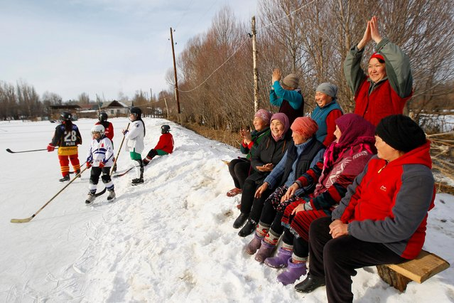 Supporters of Kyrgyzstan's first female hockey team cheer during a training match in the village of Otradnoye, Kyrgyzstan on February 4, 2020. (Photo by Vladimir Pirogov/Reuters)