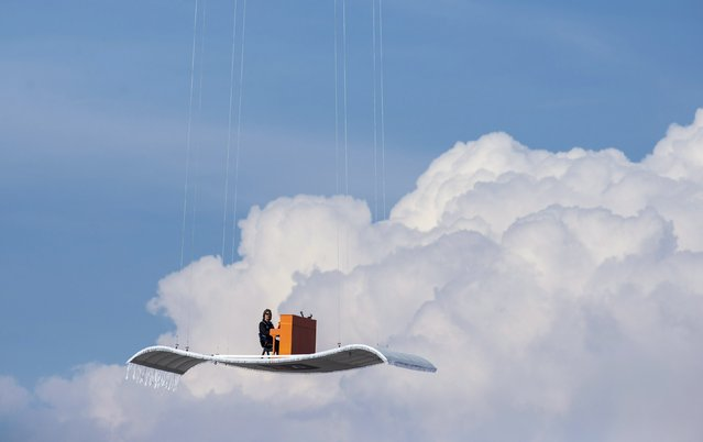 """German pianist Stefan Aaron plays an orange piano on a """"flying carpet"""" platform suspended from a helicopter, over the Munich airport July 23, 2014. The concert is the fourth station of the """"Orange Piano Tour"""", which brings the artist to places around the world. (Photo by Lukas Barth/Reuters)"""