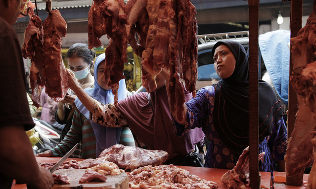 Muslim women shop for meat in preparation of the upcoming Eid al-Fitr holiday that marks the end of the holy fasting month of Ramadan, at a market in Jakarta, Indonesia, Friday, June 23, 2017. (Photo by Achmad Ibrahim/AP Photo)