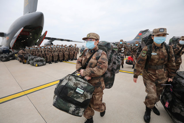 Military medics arrive at Tianhe International Airport in Wuhan, central China's Hubei Province, February 13, 2020. Ordered by the Central Military Commission, 11 transport aircraft of the People's Liberation Army Air Force Thursday sent medics and supplies provided by the armed forces to virus-hit Wuhan, capital of Hubei Province. This was the first time for China's domestically developed large transport aircraft Y-20 to take part in non-military action. It was also the first time for the Air Force to send large and medium transport aircraft on active service to carry out urgent air transport tasks on a large scale. (Photo by Reuters/China Stringer Network)