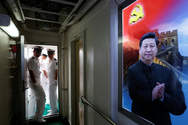 People's Liberation Army naval soldiers stand inside a military vessel at a naval base featuring a photo of Chinese President Xi Jinping, during an open day celebrating the 19th anniversary of Hong Kong's handover to Chinese sovereignty from British rule, in Hong Kong July 1, 2016. (Photo by Bobby Yip/Reuters)