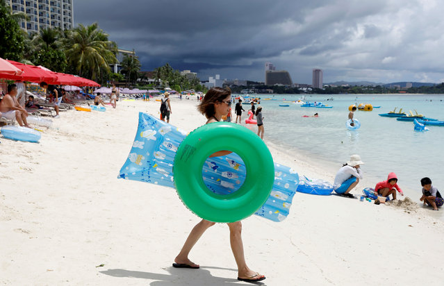 Tourists frolic along the Tumon beach on the island of Guam, a U.S. Pacific Territory, August 10, 2017. North Korea said it is finalizing a plan to launch a salvo of four ballistic missiles off the shores of the U.S. territory of Guam, the latest provocation in the war of words between Pyongyang and Washington. (Photo by Erik De Castro/Reuters)