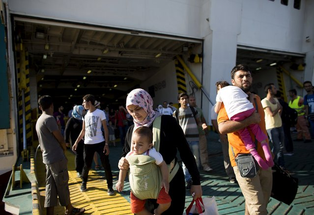 """A Syrian refugee family walks out of """"Eleftherios Venizelos"""" passenger ship after its arrival at the port of Piraeus near Athens, Greece, August 20, 2015. (Photo by Stoyan Nenov/Reuters)"""