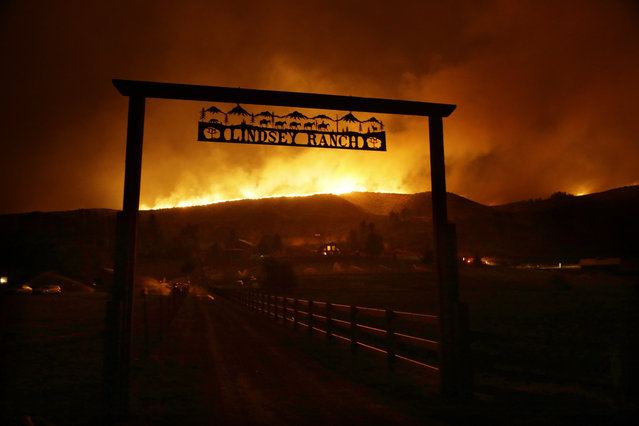 Fire burns on the ridge above a ranch on Twisp River Road in Twisp, Wash., Wednesday, August 19, 2015. Authorities on Wednesday afternoon urged people in the north-central Washington town to evacuate because of a fast-moving wildfire. (Photo by Ted S. Warren/AP Photo)