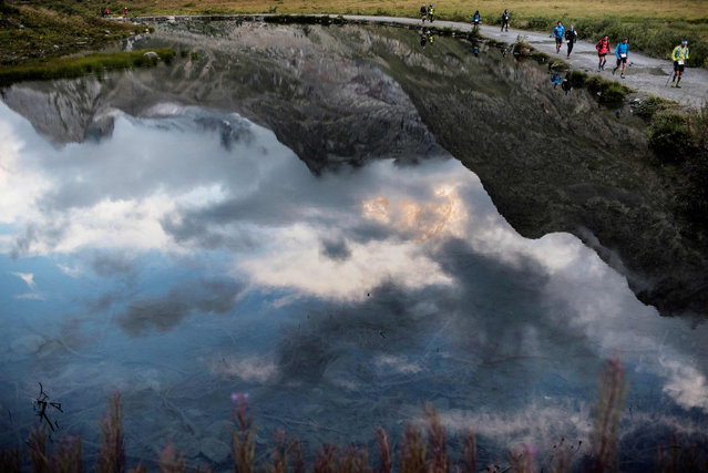 Ultra- trailers compete past the Combal lake at sunrise on September 2, 2017 in Courmayeur, Italy, during the 15 th edition of the Mount Blanc Ultra Trail (UTMB), a 170 km race around the Mont Blanc crossing France, Italy and Switzerland. (Photo by Jeff Pachoud/AFP Photo)