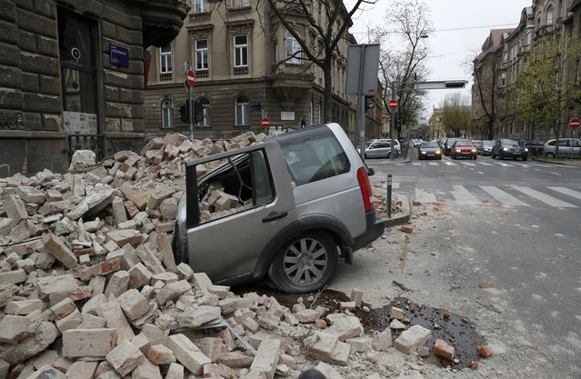 A car is crushed by falling debris after an earthquake in Zagreb, Croatia, Sunday, March 22, 2020. A strong earthquake shook Croatia and its capital on Sunday, causing widespread damage and panic. (Photo by Darko Bandic/AP Photo)