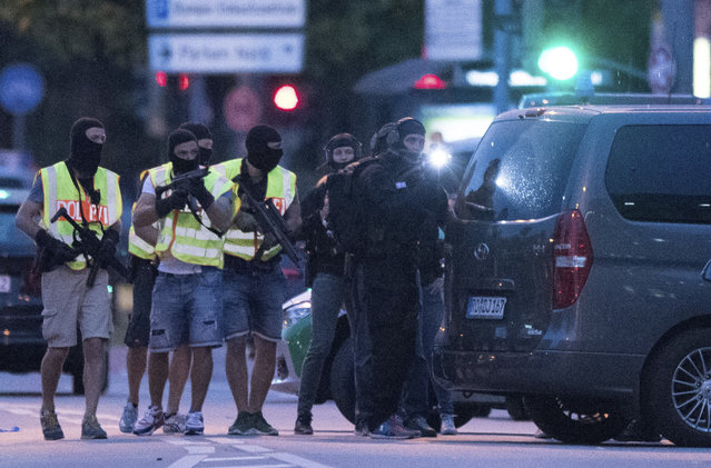 People leave the Olympia mall in Munich, southern Germany, Friday, July 22, 2016 after several people have been killed in a shooting. (Photo by Sebastian Widmann/AP Photo)