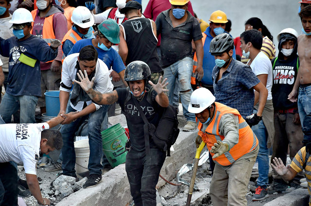 Rescuers, firefighters, policemen, soldiers and volunteers remove rubble and debris from a flattened building in search of survivors after a powerful quake in Mexico City on September 19, 2017. A devastating quake in Mexico on Tuesday killed more than 100 people, according to official tallies, with a preliminary 30 deaths recorded in the capital where rescue efforts were still going on. (Photo by Yuri Cortez/AFP Photo)