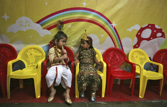 "School children dressed as Lord Krishna (L) and Goddess Radha sit in their classroom during the celebrations on the eve of the Hindu festival ""Janmashtami"" in Jammu August 9, 2012. (Photo by Mukesh Gupta/Reuters)"