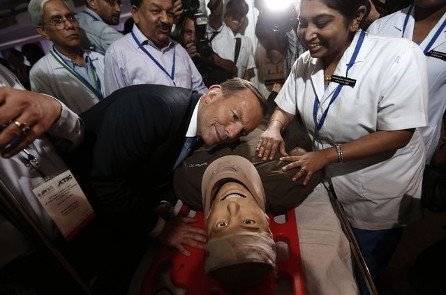Australia's Prime Minister Tony Abbott (C) takes part in a presentation with a patient simulator during his visit to the trauma centre of the All India Institutes of Medical Sciences (AIIMS) in New Delhi September 5, 2014. Abbott said he would seal a civil nuclear deal to sell uranium to India on Friday, offering to ramp up supplies of energy to help the emerging Asian giant overcome chronic shortages. (Photo by Adnan Abidi/Reuters)